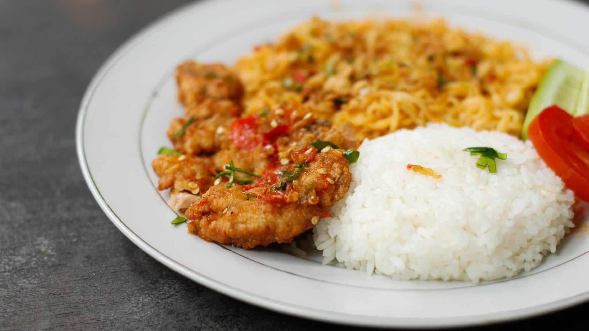 Noodles met vlees en witte rijst op een bordje