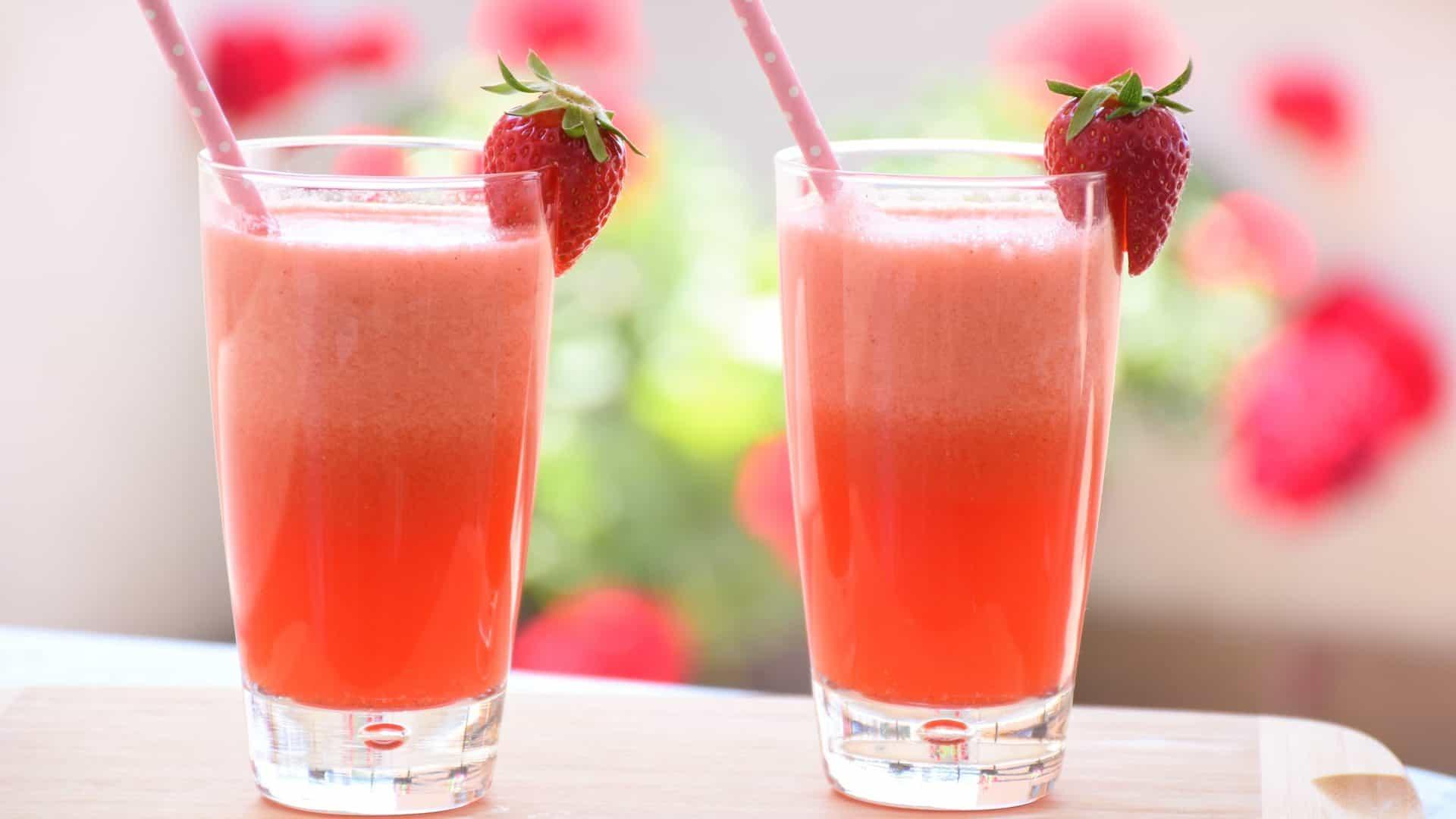 Twee glazen met rood, helder sap met een aardbei en een rietje.