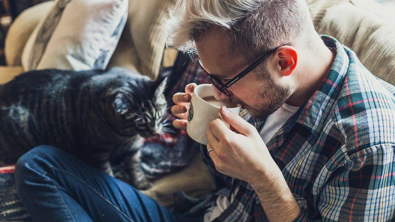 Man die koffie drinkt op de bank, met kat ernaast. Zij-aanzicht