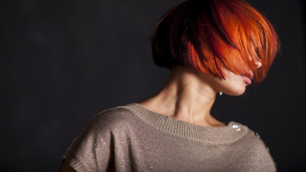 Vrouw met kort, rood haar over gezicht