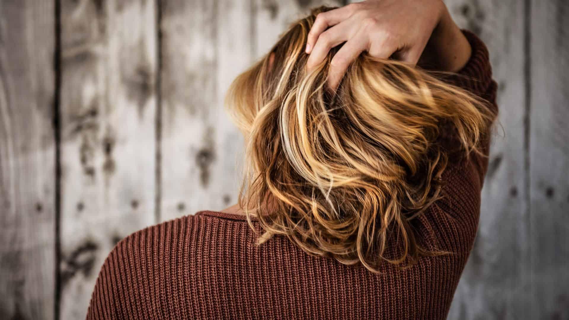 Persoon met handen in het (blonde) haar, vanaf achterzijde.