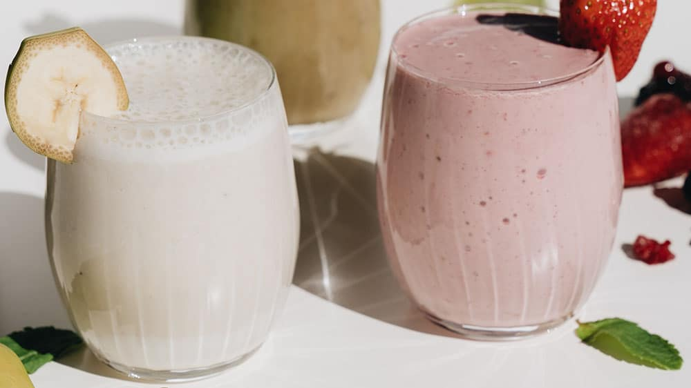 Afbeelding van twee glazen met verschillende smoothies erin en een stukje fruit ter decoratie op de rand.