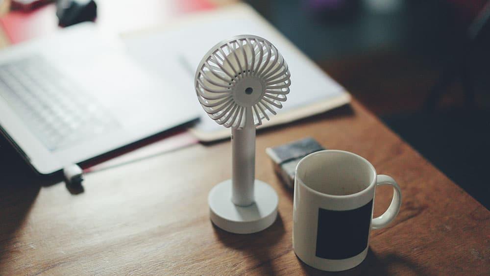 Afbeelding van een kleine ventilator op een tafel.