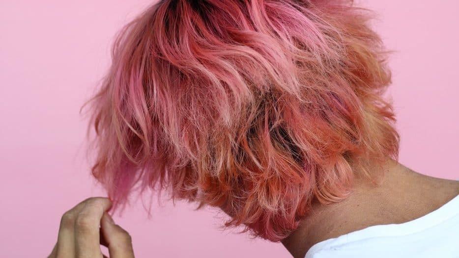 Jongen met roze haar tegen roze achtergrond
