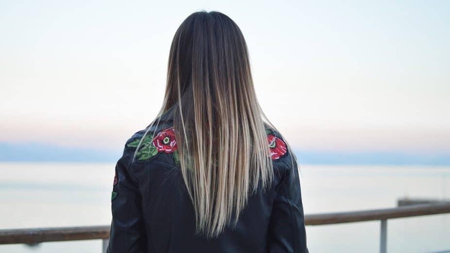 Vrouw met leren jasje aan met stijl haar van donker naar licht geverfd
