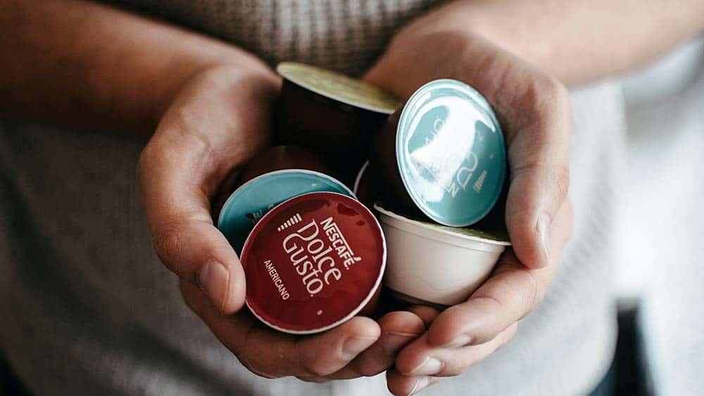 Afbeelding van handen die Dolce gusto cups vasthouden.