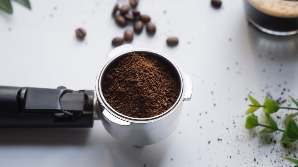 Gemalen koffie tegen een witte achtergrond