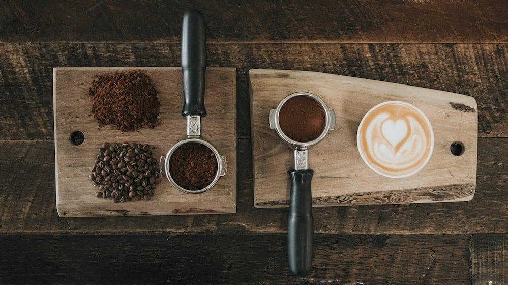 Houten plank met koffie, gemalen koffie en koffiebonen erop