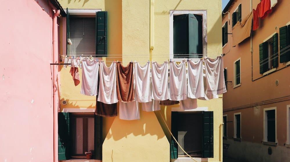 Kleding aan een waslijn tussen gekleurde huizen
