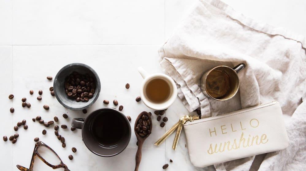 Verschillende kopjes koffie en koffiebonen tegen een witte achtergrond
