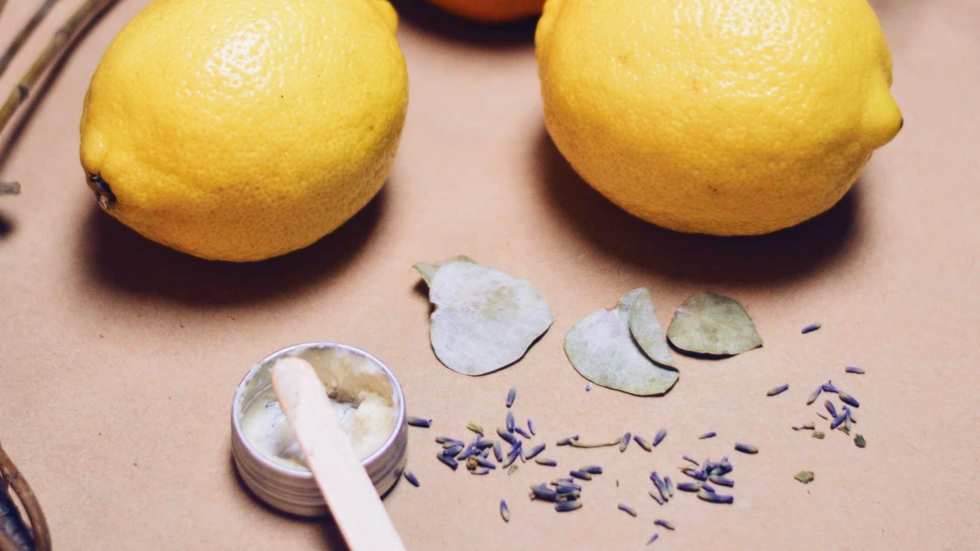 Twee citroenen met daaronder een klein potje crème en spatel. Op lichtbruine achtergrond, bovenaanzicht.