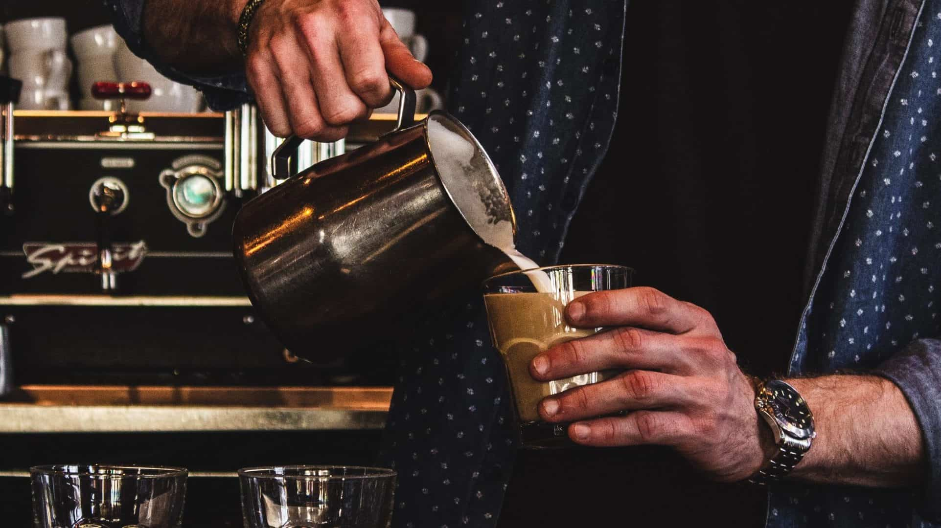 Persoon giet opgeschuimde melk in glas koffie.