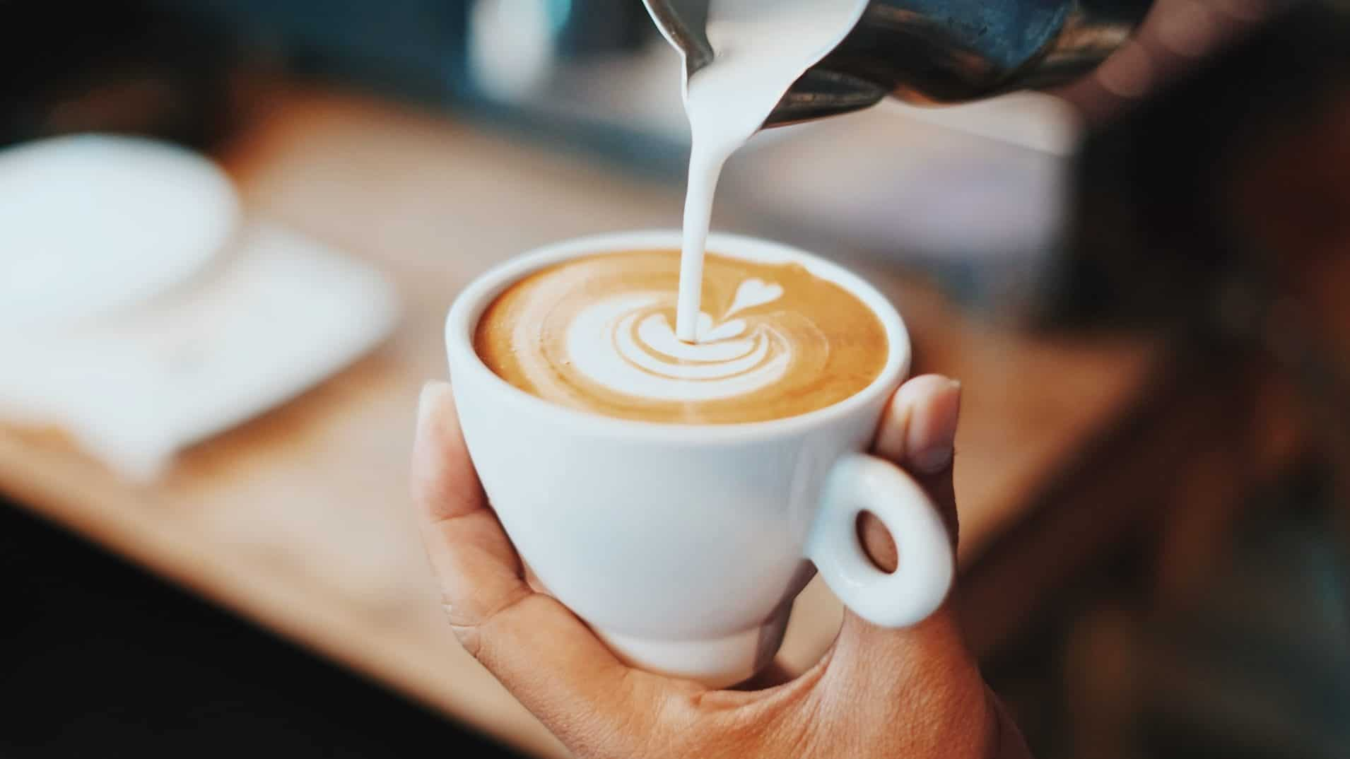 Kopje koffie met melkschuim wat geschonken wordt. Vooraanzicht.