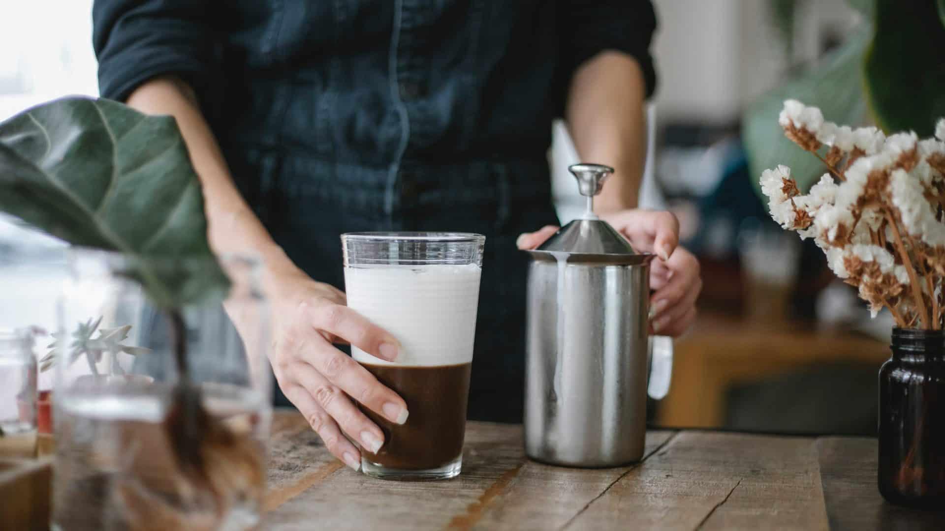 Glas koffie met romige laag melkschuim en een hand melkopschuimer.