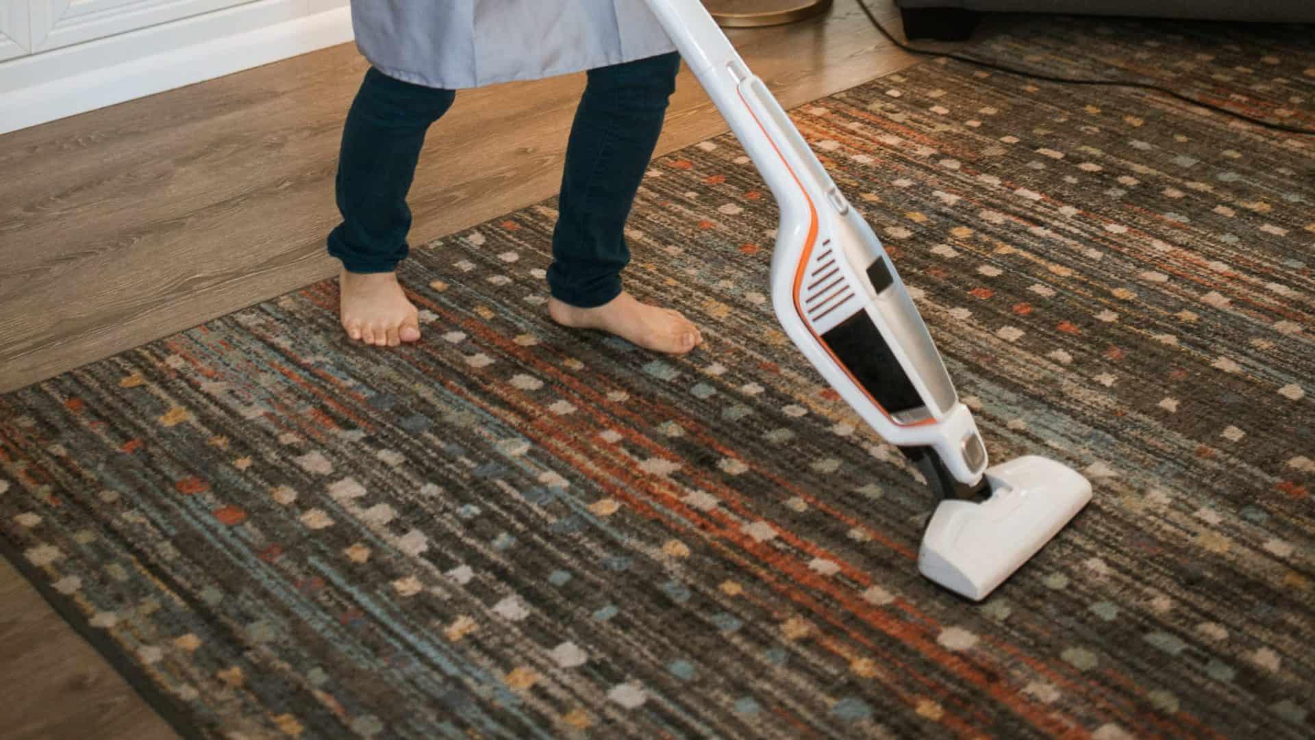 Persoon stofzuigt tapijt.
