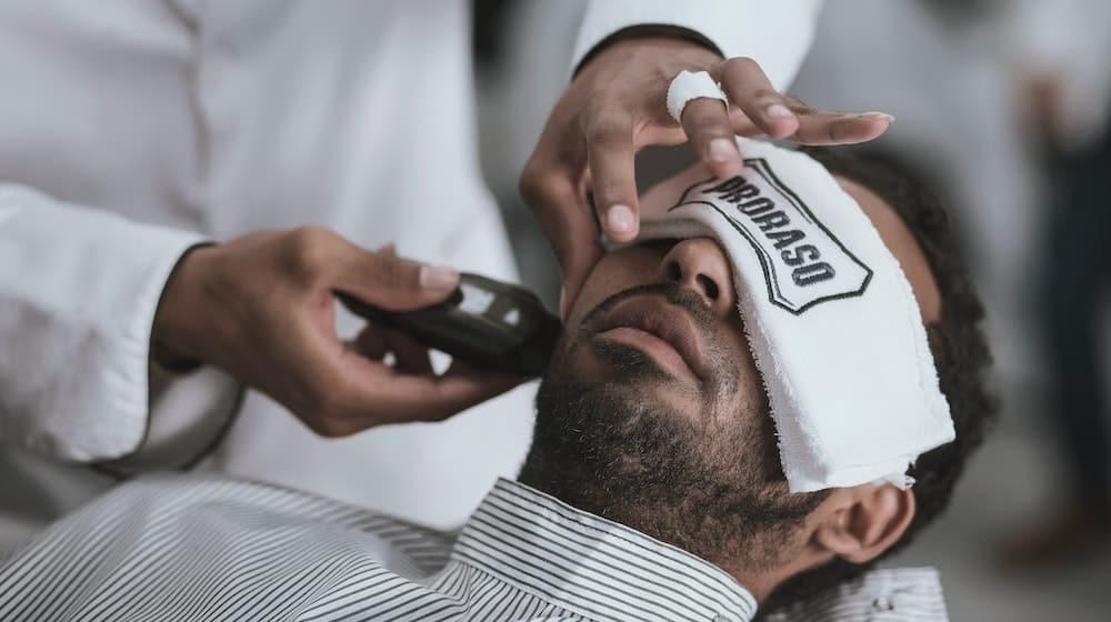 Baard wordt geschoren van man door kapper