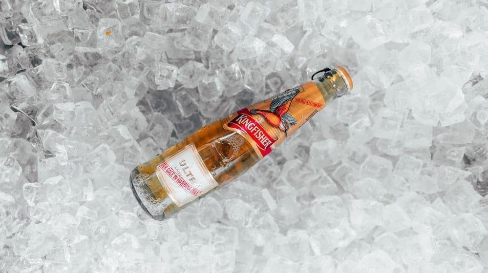 Bierflesje op achtergrond van ijsklontjes