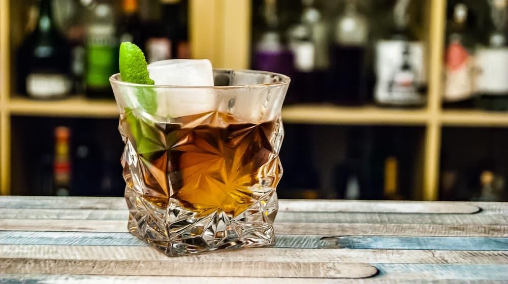 Cocktail met ijs en blaadje op houten bar