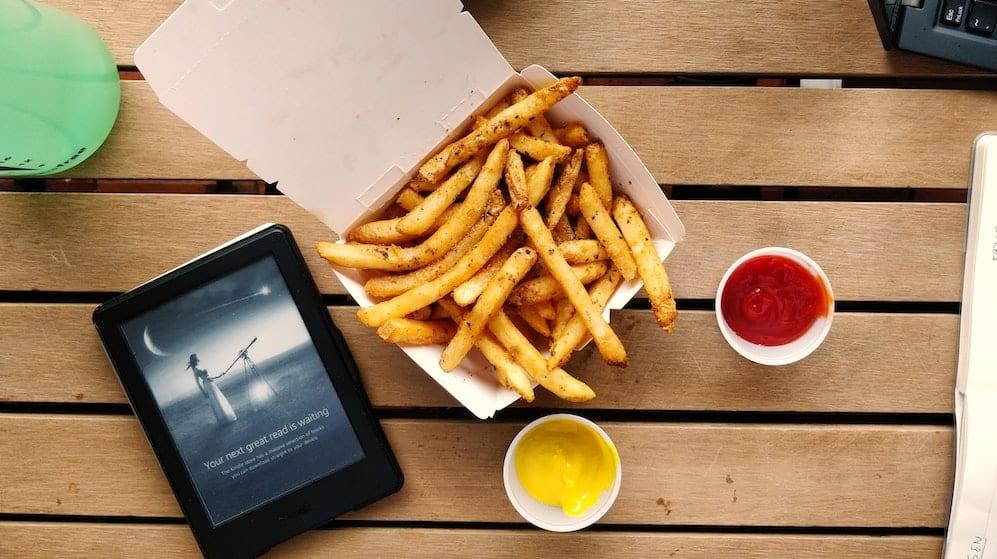 Frietjes op een houten tafel met een tablet ernaast