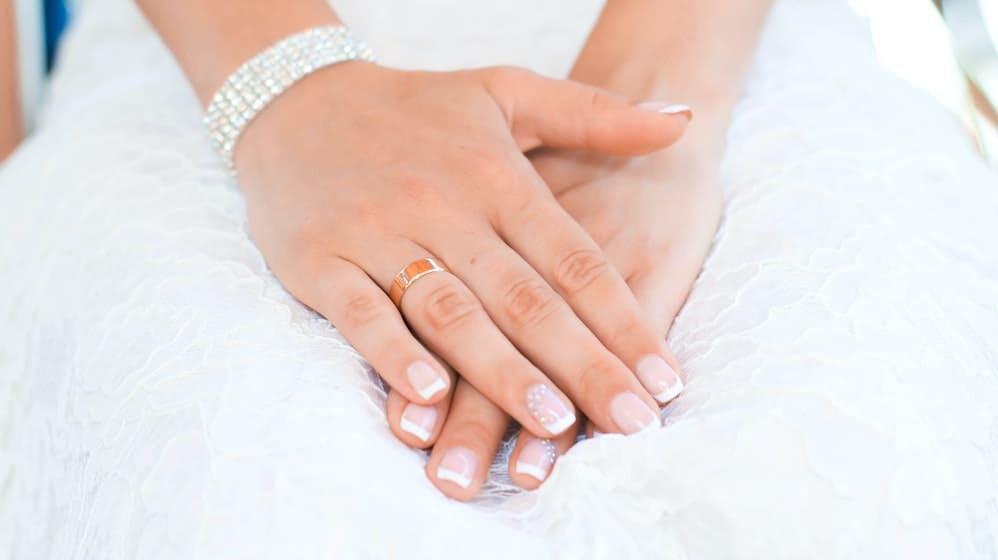 Handen die manicure hebben gehad op trouwjurk achtergrond