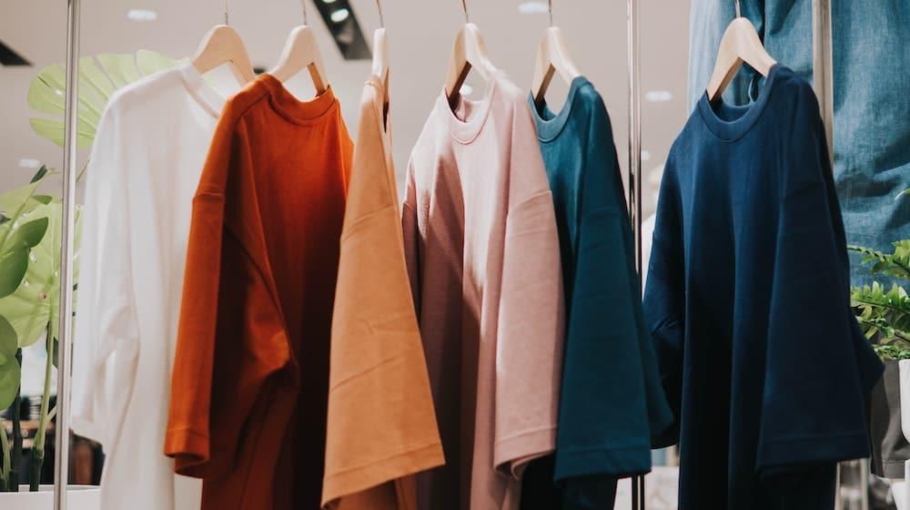 Kleding in verschillende kleuren aan kledinghanger
