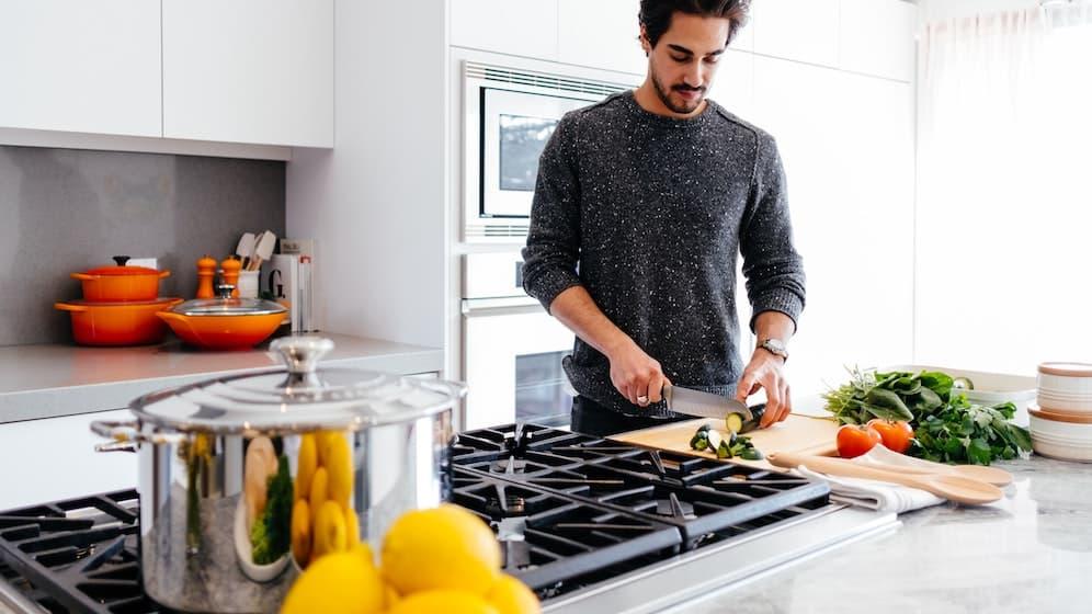 Man die groenten snijdt in keuken