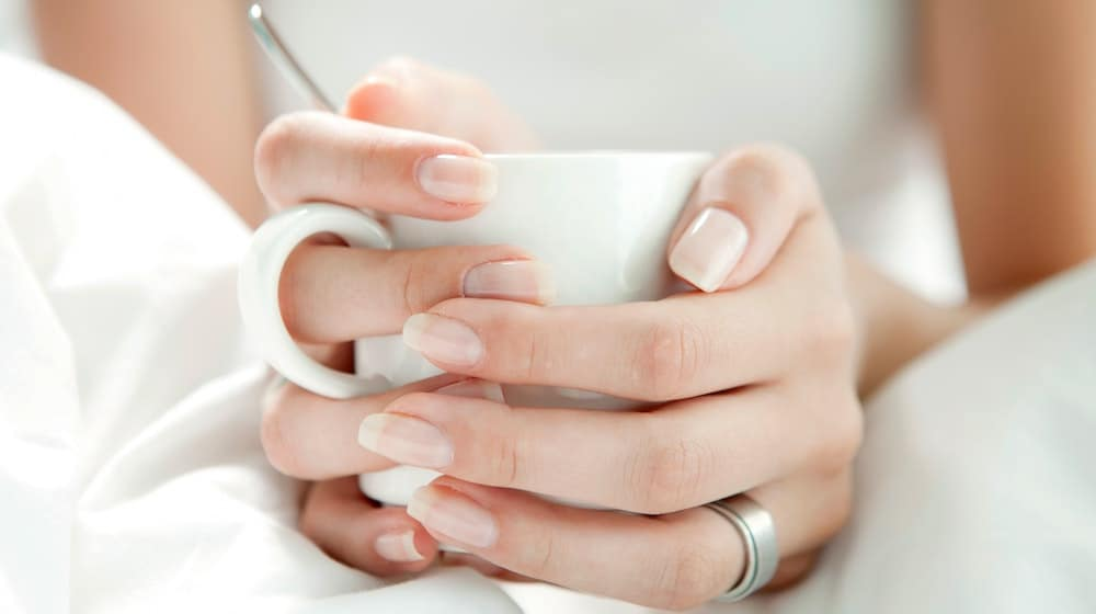 Mooie nagels van vrouw die kopje vasthoudt in bed