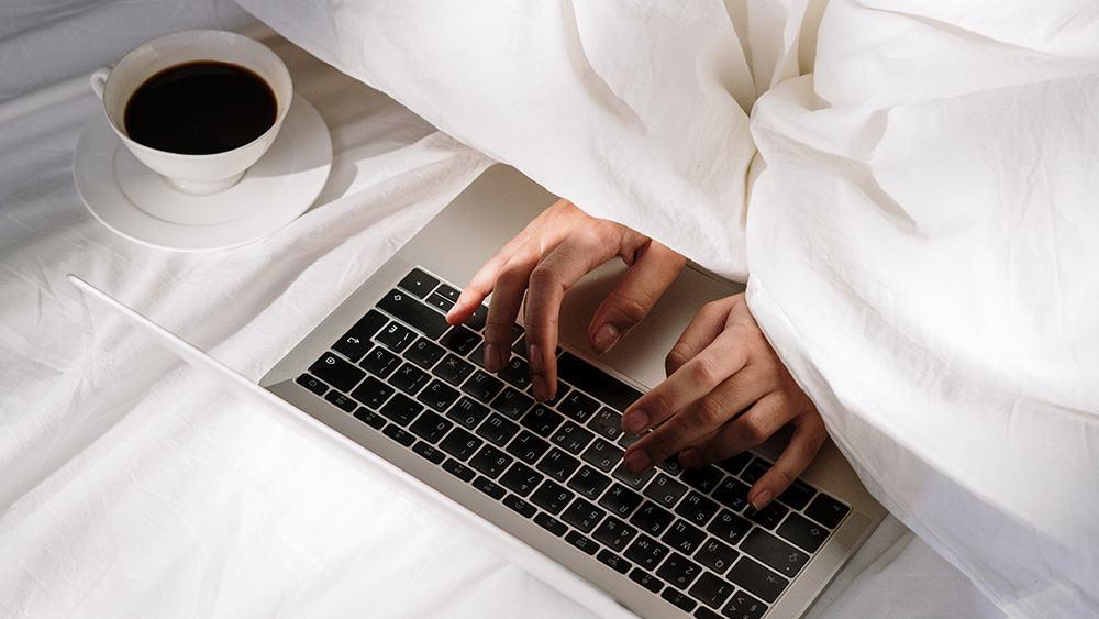 Afbeelding van iemand die op bed zit en typt op een laptop, met een kop koffie naast zich