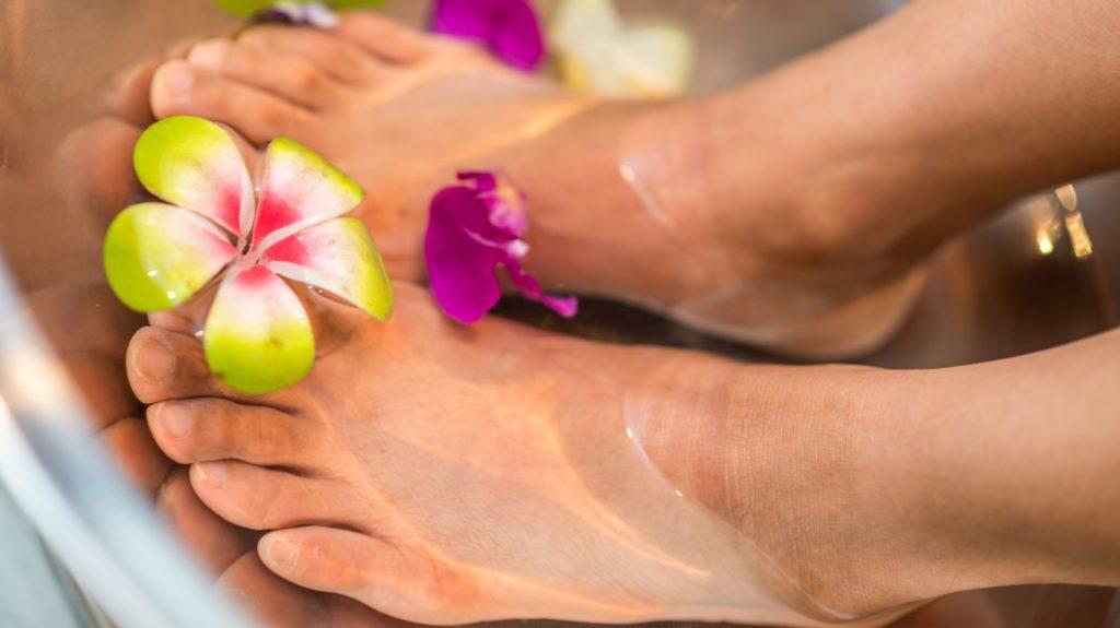 voeten in badje water met bloemen