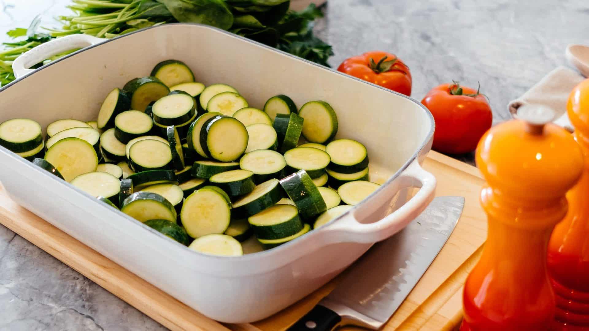 Ovenschotel met courgette. Tomaten, een mes, peper en spinazie liggen naast de ovenschotel.