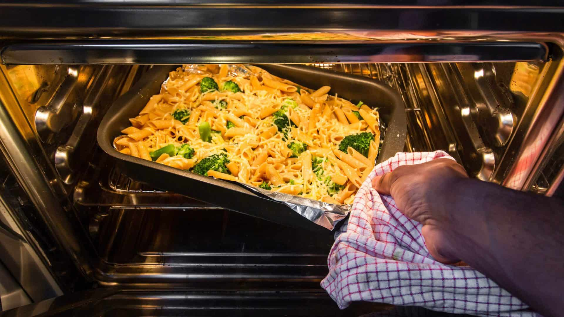 Persoon doet ovenschotel met pasta, kaas en broccoli in de oven.