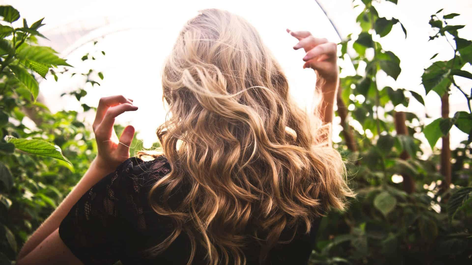 Persoon met golfjes in het haar staat buiten en rijkt met handen naar het haar.