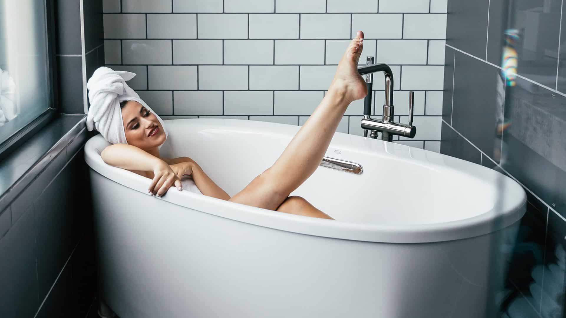 Afbeelding van een vrouw in bad met een handdoek op haar hoofd. Ze strekt een been omhoog.