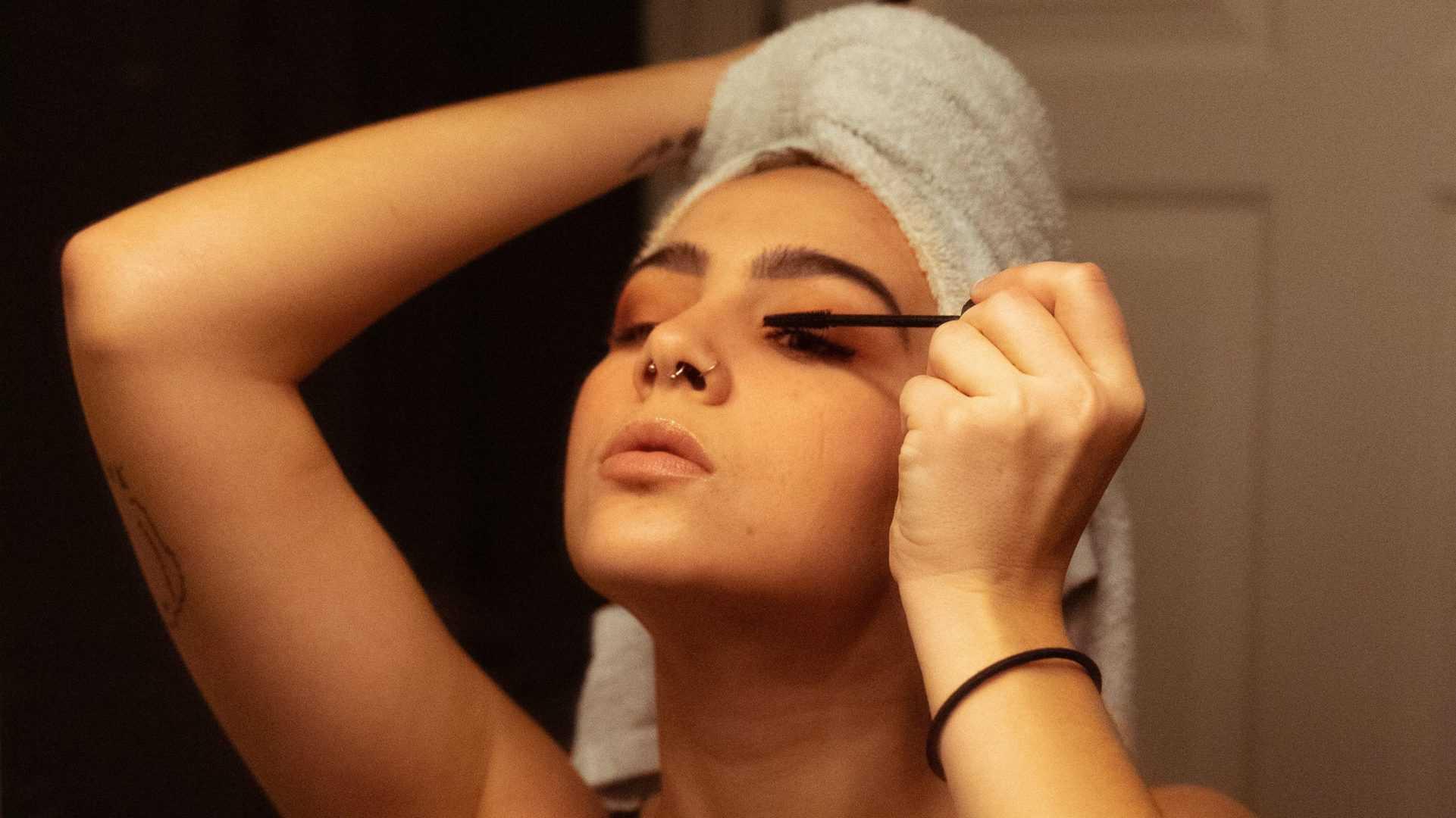 Persoon met een handdoek om het hoofd doet mascara op