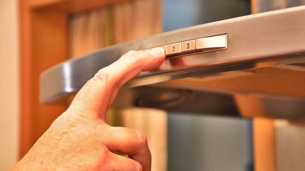 Afbeelding van een hand die knopjes indrukt op de rand van een afzuigkap.